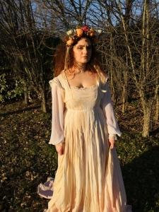 foto fine art di una donna dai capelli rossi con vestito bianco lungo e copricapo di fiori