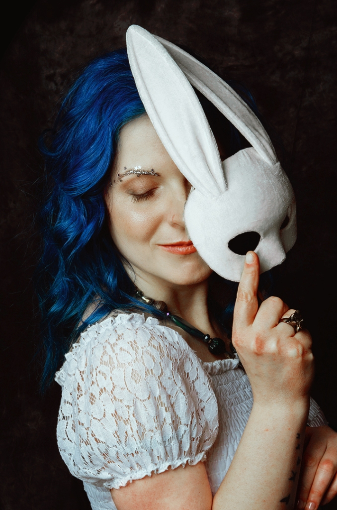 Ritratto fotografico fine art rappresentante una donna dai capelli blu con una maschera da coniglio bianco