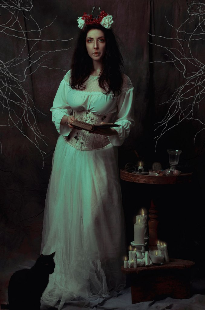 ritratto fotografico fine art di erica mottin rappresentante una donna con abito bianco con in mano un libro aperto accanto ad un altare e con un gatto nero ai suoi piedi