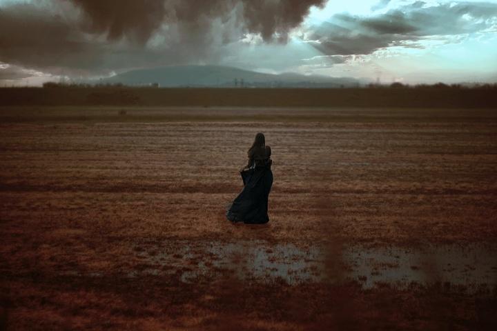 ritratto fotografico fine art di erica mottin rappresentante una donna strega in una palude con indosso un vestito nero