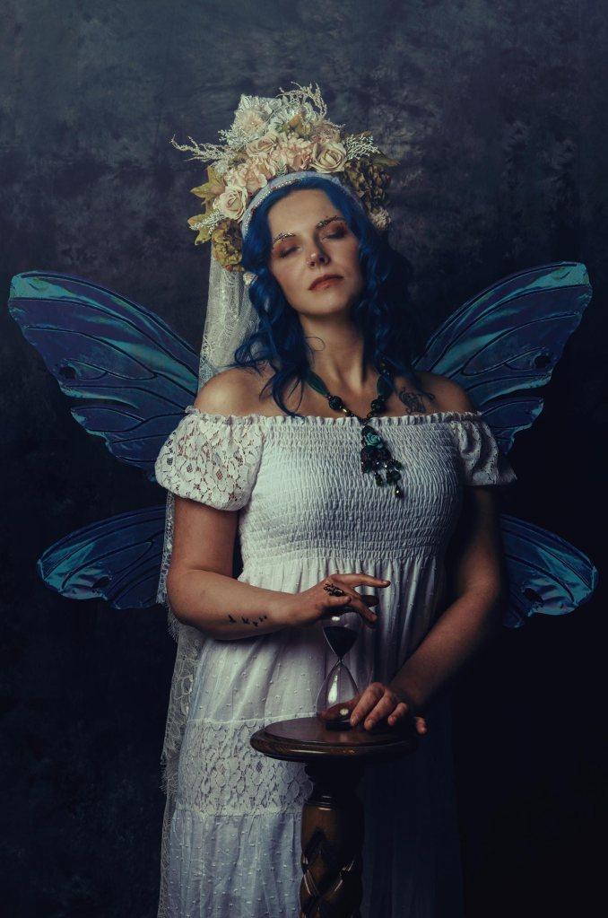 ritratto fotografico fine art di erica mottin rappresentante una donna con i capelli blu ed un vestito bianco con ali da fata con in mano una clessidra e un copricapo bianco realizzato da Giorgia Titania