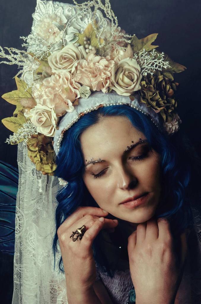 ritratto fotografico fine art di erica mottin rappresentante una donna con i capelli blu ed un vestito bianco con ali da fata e un copricapo bianco realizzato da Giorgia Titania