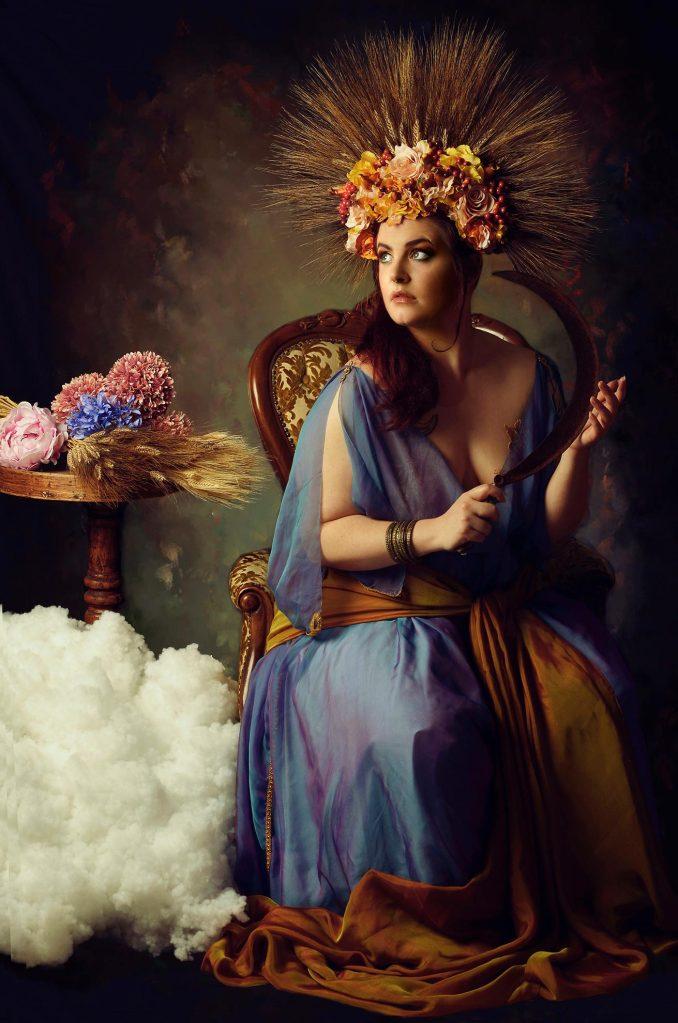 Ritratto fotografico fine art fantasy di Erica Mottin realizzato in collaborazione con la designer Elaine's Couture e rappresentante una donna seduta su una poltrona con ai piedi nuvole di cotone, in mano un falcetto e un headdress di spighe di grano e fiori