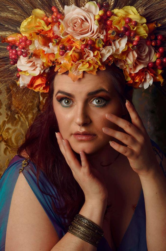 Ritratto fotografico fine art fantasy di Erica Mottin realizzato in collaborazione con la designer Elaine's Couture e rappresentante una donna dai capelli rossi e occhi verdi con un copricapo di giori e spighe di grano
