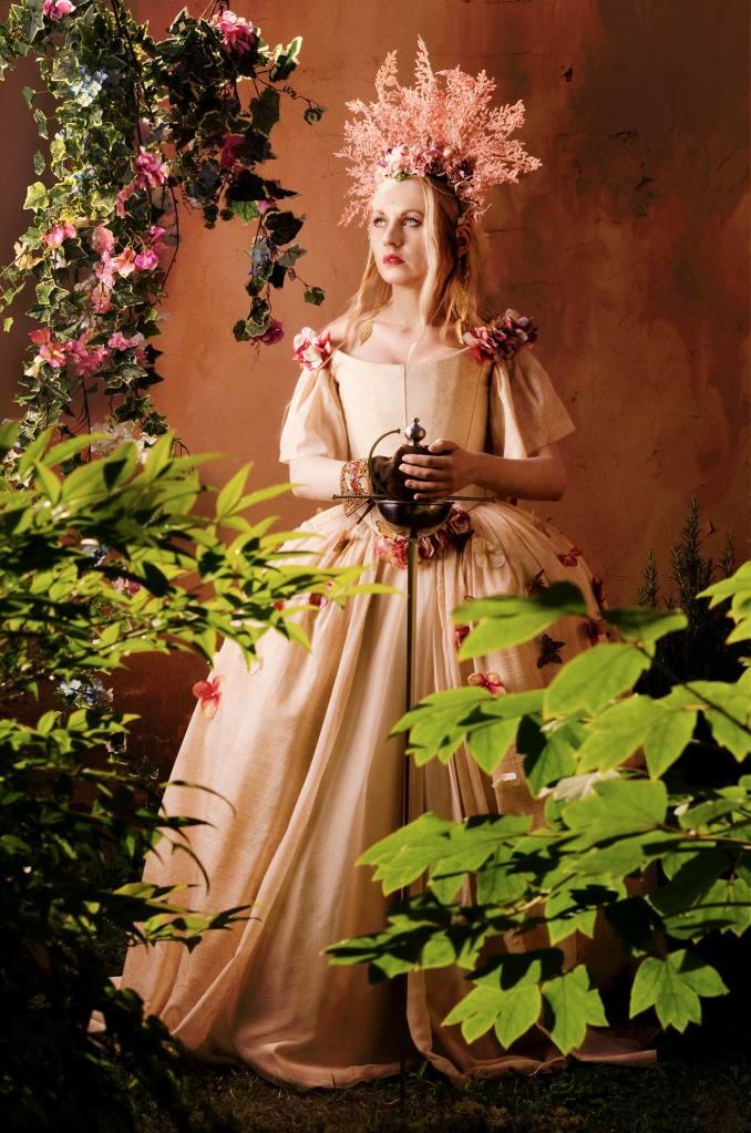 ritratto fotografico fine art fantasy di erica mottin rappresentante una donna dai capelli biondi e occhi celesti in abito con fiori e headdress con fiori realizzato da elaine's couture circondata da piante e con in mano una spada realizzata da Malleus Martialis