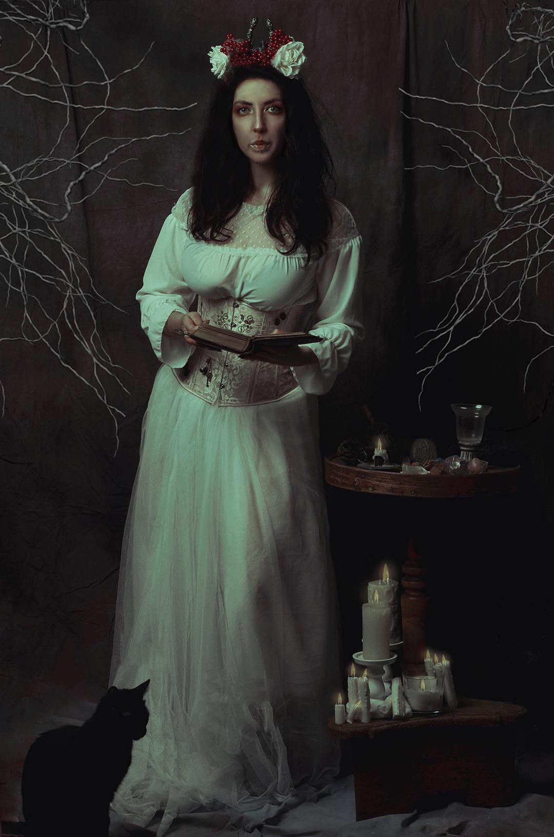 Ritratto fotografico fine art Firenze di Erica Mottin rappresentante una donna nelle vesti di una dea pagana con altare candele e un gatto nero