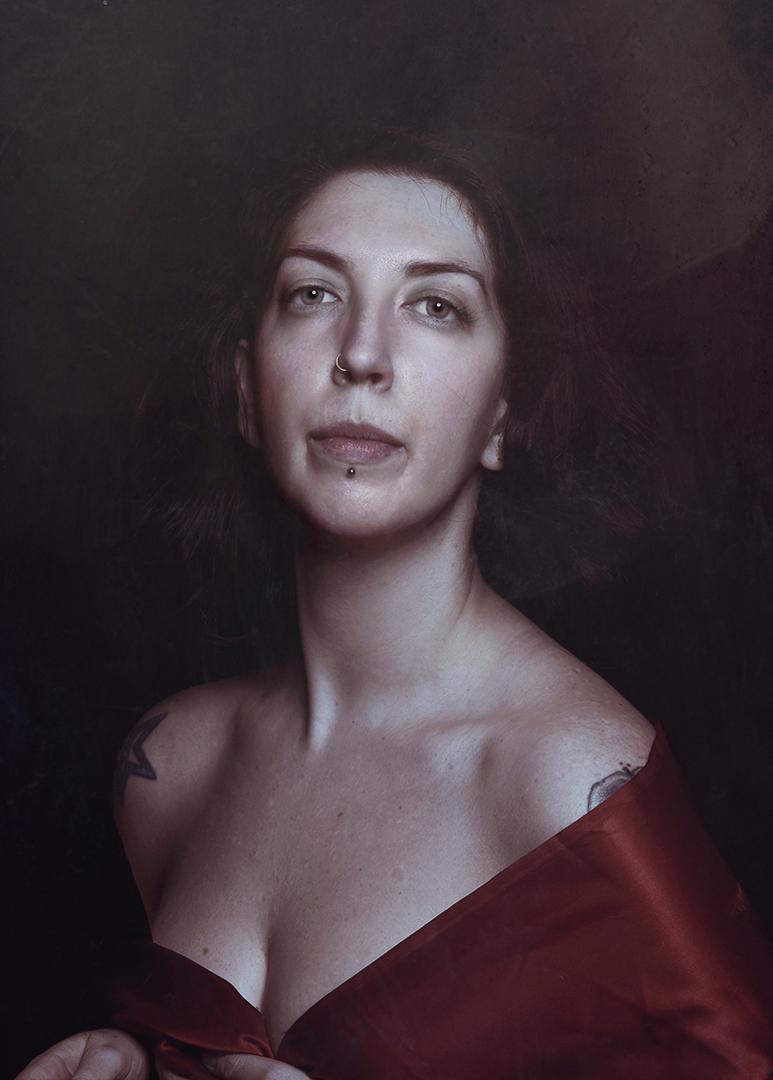 ritratto fotografico fine art firenze di Erica Mottin rappresentante una donna con tatuaggi e piercings coperta da un telo satinato rosso