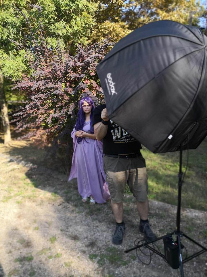 Corsi di fotografia fine art firenze in location con modella che indossa un abito viola e una parrucca viola con flash quadralite e octabox godox