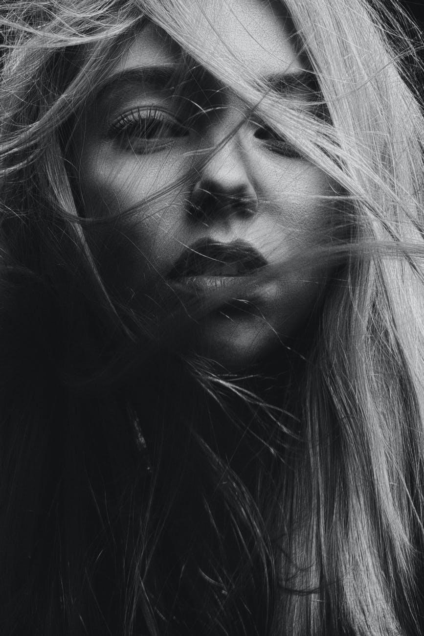 ritratto fotografico in bianco e nero di donna con capelli biondi sul viso