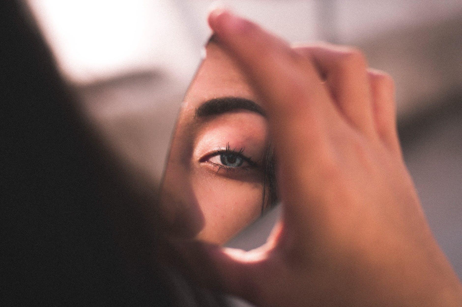 ritratto fotografico fine art di donna che tiene in mano uno specchio rotto dove si specchia il suo occhio azzurro