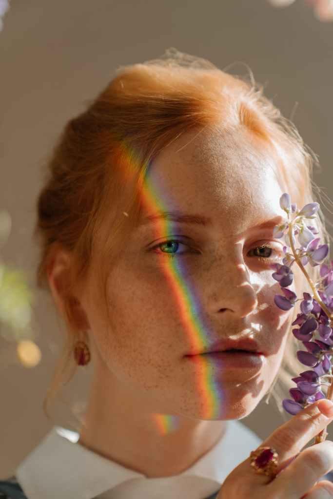 ritratto fotografico fine art donna dai capelli rossi con arcobaleno sugli occhi e un fiore di lilla