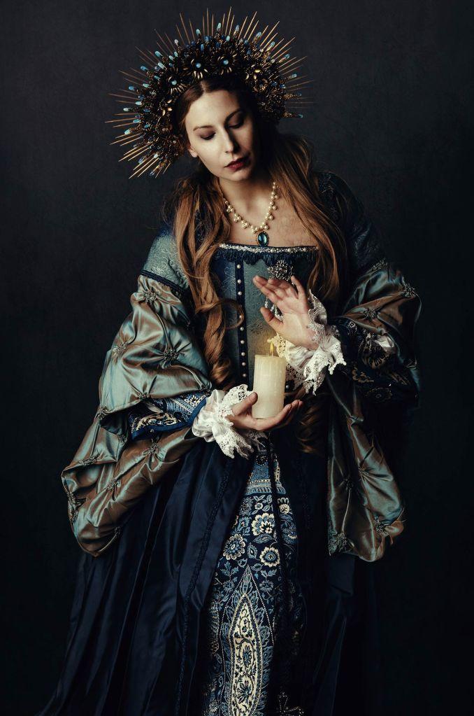 ritratto fotografico fine art rappresentante una donna in abito storico con corona di pietre oro e blu con in mano una candela