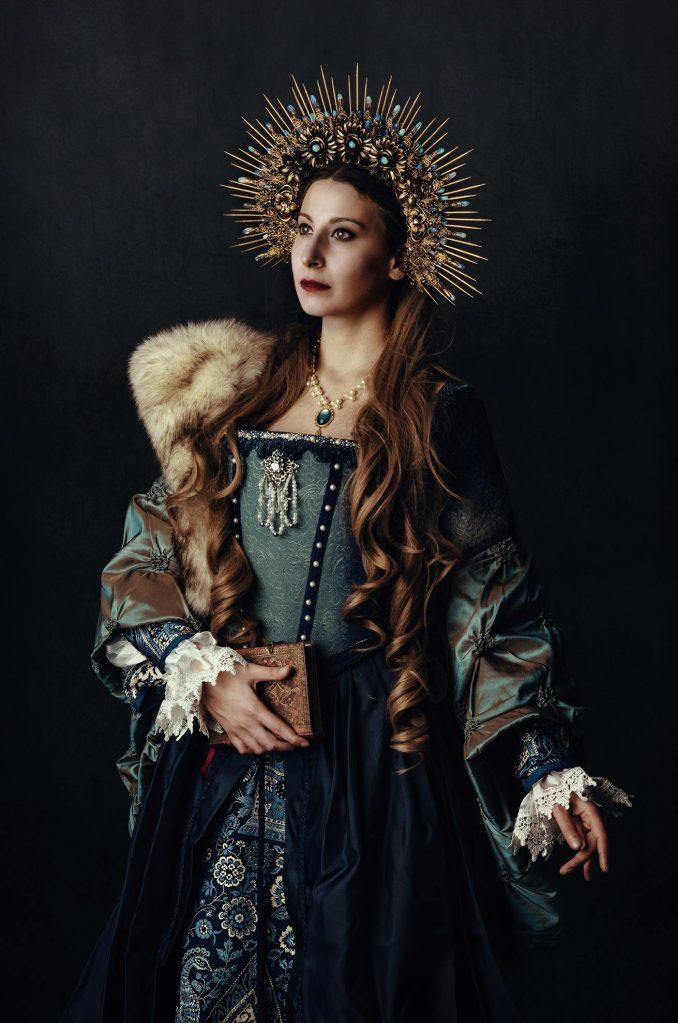 ritratto fotografico fine art rappresentante una donna in abito storico con corona di pietre oro e blu con in mano una libro antico