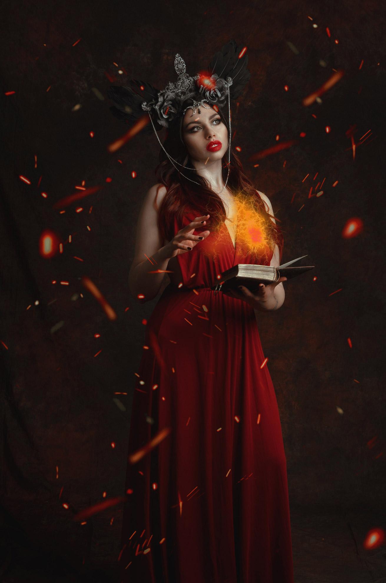 ritratto fotografico fine art dark fantasy di erica mottin rappresentante una donna in abito rosso con headdress di piume nere creato da Giorgia Titania con in mano un libro che sta lanciando un incantesimo