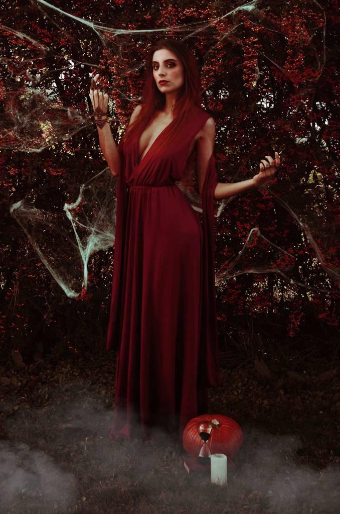 ritratto fotografico fine art dark fantasy rappresentante una donna strega dai capelli rossi con vestito rosso in un bosco con nebbia e ragnatele