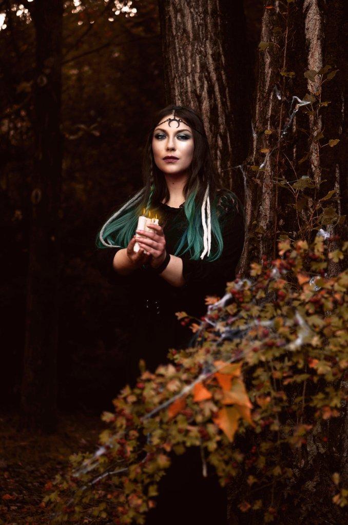 ritratto fotografico fine art fantasy rappresentante una donna strega in un bosco autunnale con capelli verde acqua e candele tra le mani