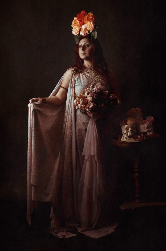 ritratto fotografico fine art di erica mottin rappresentante una donna nelle vesti di persefone con in mano un mazzo di fiori rosa e un altare di lego con dei teschi