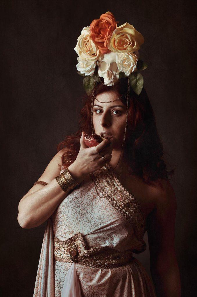 ritratto fotografico fine art di erica mottin rappresentante una donna nelle vesti di persefone con in mano una melagrana con l'intento di mangiarla