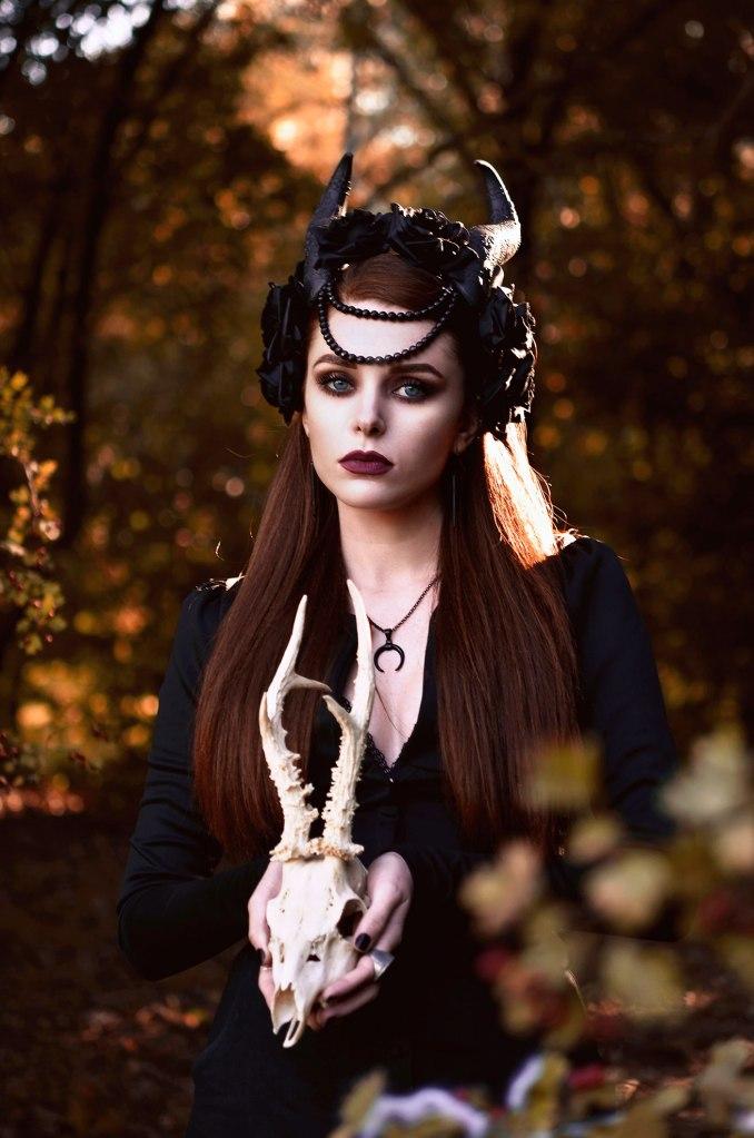 ritratto fotografico fine art rappresentante una donna in un bosco autunnale nei panni di una strega con copricapo di corna e un teschio di animale in mano