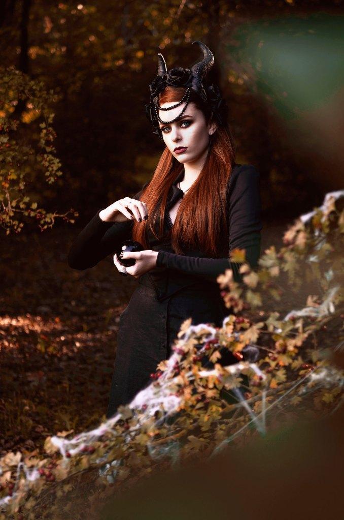 ritratto fotografico fine art rappresentante una donna strega in un bosco autunnale nei panni di una strega con copricapo di corna e una sfera di ossidiana nera in mano