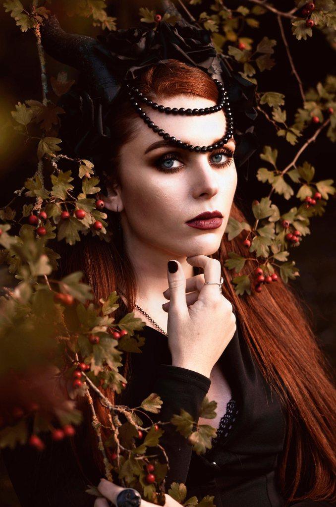 ritratto fotografico fine art fantasy rappresentante una donna con i capelli rossi e un copricapo di corna nere e rose nere in mezzo ad un cespuglio con bacche rosse