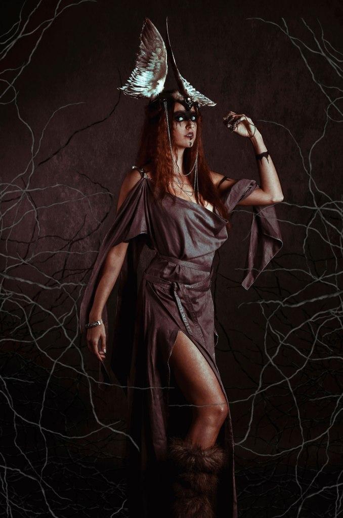 ritratto fotografico fine art rappresentante una donna vichinga dai capelli rossi con copricapo alato e rami di albero che la avvolgono