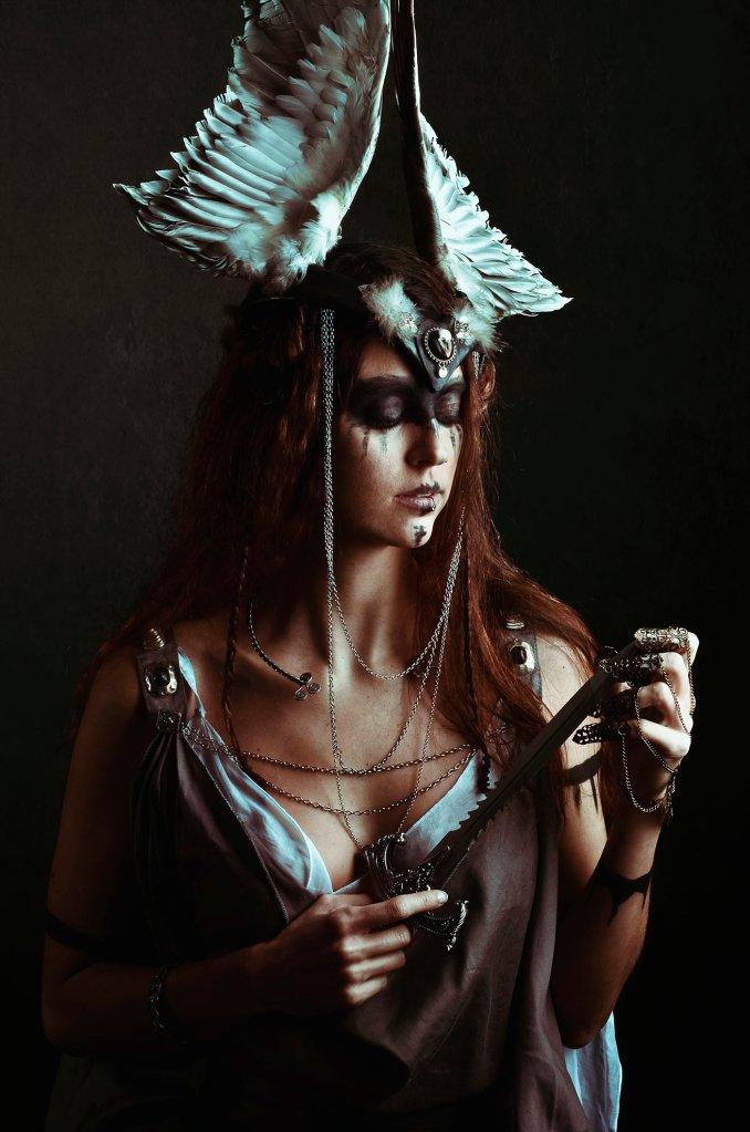 ritratto fotografico fine art rappresentante una donna guerriera vichinga dai capelli rossi con copricapo alato e in mano un pugnale