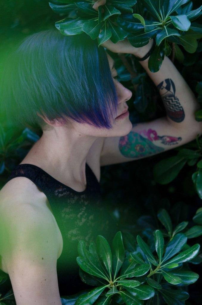 ritratto fotografico fine art di erica mottin rappresentante una donna dai capelli viola con tatuaggi colorati in un cespuglio verde