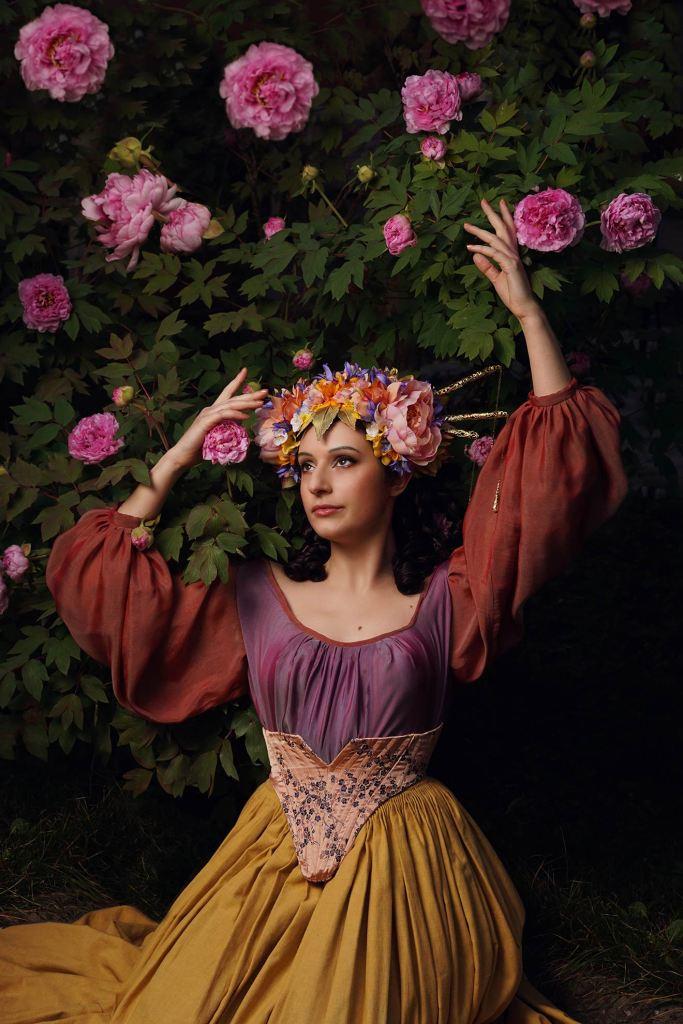 ritratto fotografico fine art fantasy di erica mottin realizzato in collaborazione con Elaine's Couture rappresentante una donna con un corpicapo di fiori rosa e viola e gialli e foglie d'oro in un cespuglio di peonie