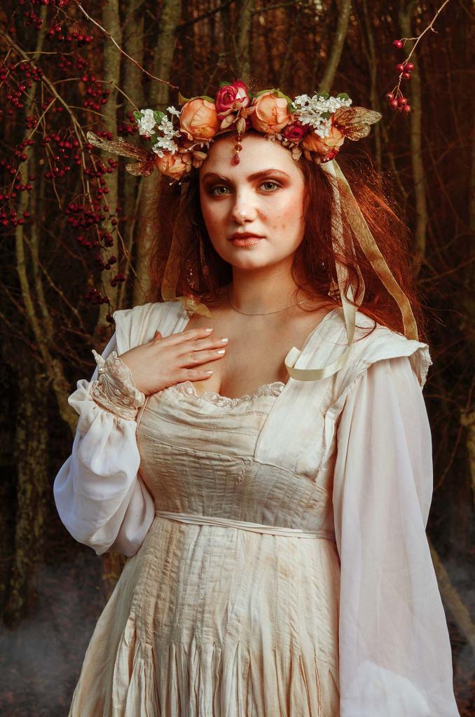ritratto fotografico fine art fantasy rappresentante una fata dai capelli rossi con copricapo e abito bianco lungo in una foresta