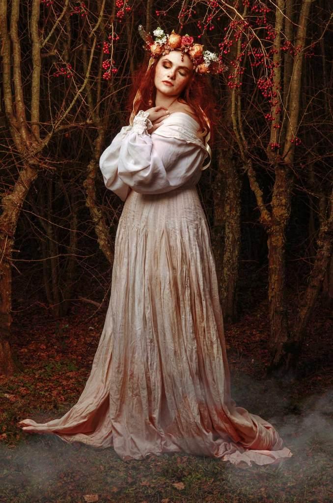 ritratto fotografico fine art di erica mottin rappresentante una donna in abito bianco con i capelli rossi e un headdress fatato in mezzo ad un bosco oscuro