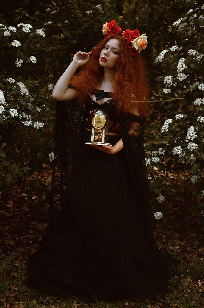 ritratto fotografico fine art fantasy di erica mottin rappresentante una donna dai capelli rossi e mossi e la pelle bianca in una foresta con cespugli di fiori bianchi e un vestito nero che tiene in mano un orologio antico