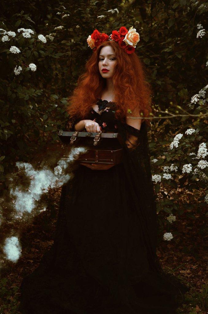 ritratto fotografico fine art fantasy di erica mottin rappresentante una donna dai capelli rossi e mossi e la pelle bianca in una foresta con cespugli di fiori bianchi e un vestito nero che tiene in mano un baule dal quale esce del fumo