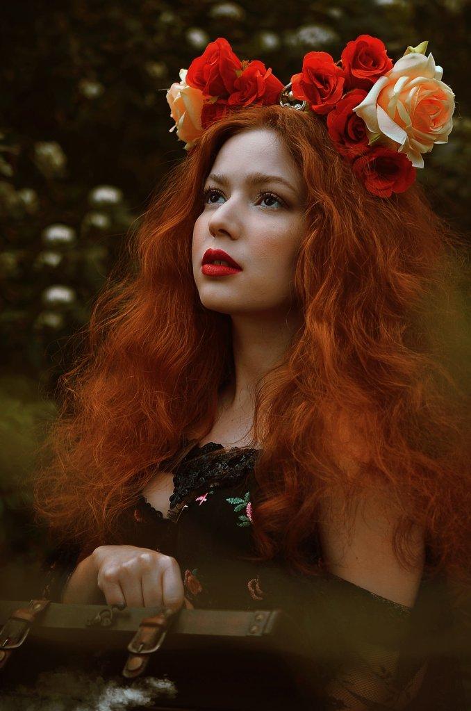 ritratto fotografico fine art fantasy di erica mottin rappresentante una donna dai capelli rossi e mossi e la pelle bianca in una foresta con cespugli di fiori bianchi e un vestito nero che tiene in mano un baule