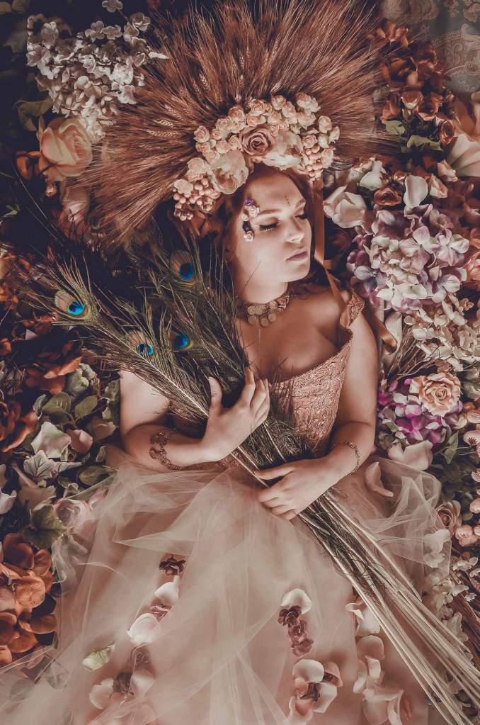 Ritratto fotografico fine art fantasy di Erica Mottin realizzato in collaborazione con la designer Elaine's Couture e rappresentante una fata in un letto di fiori con piume di pavone