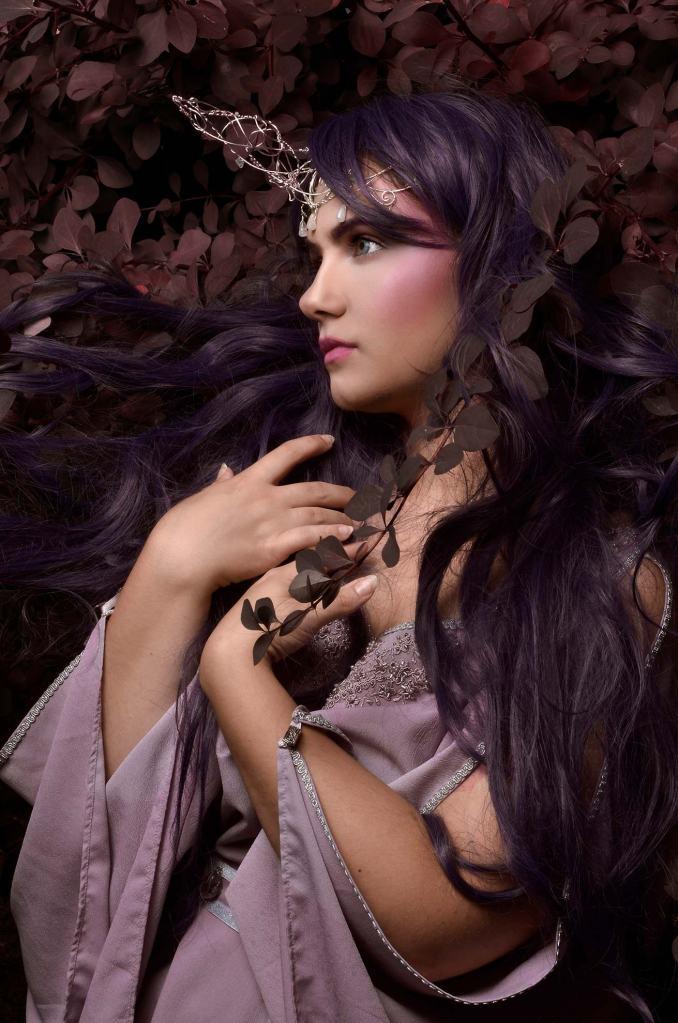 ritratto fotografico fine art fantasy che ritrare una fata dai capelli viola con un abito viola in un cespuglio di piante viola