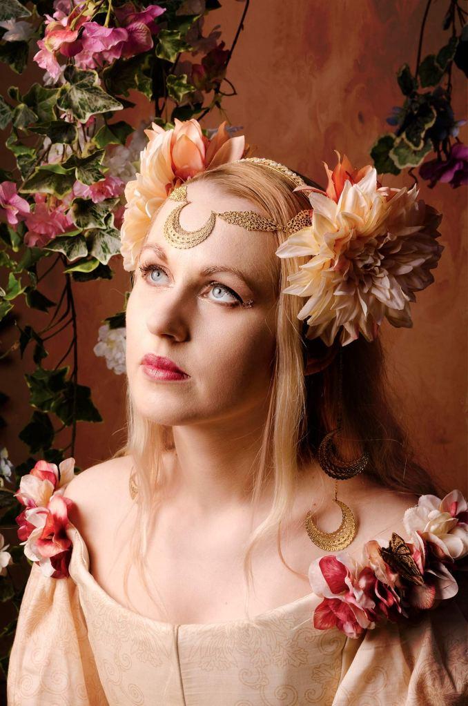 ritratto fotografico fine art fantasy di erica mottin rappresentante una donna dai capelli biondi e occhi celesti in abito con fiori e headdress con fiori realizzato da elaine's couture circondata da edera
