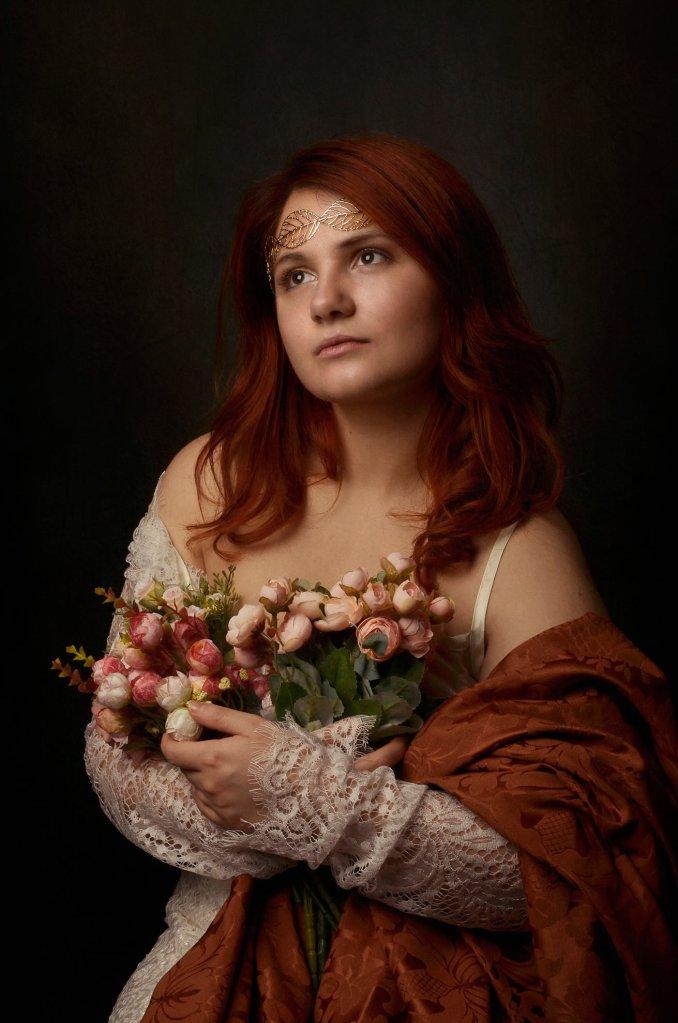 ritratto fotografico fine art di erica mottin rappresentante una donna in abito bianco e drappo rosso con capelli rossi e corona di foglie d'oro con in mano un mazzo di fiori
