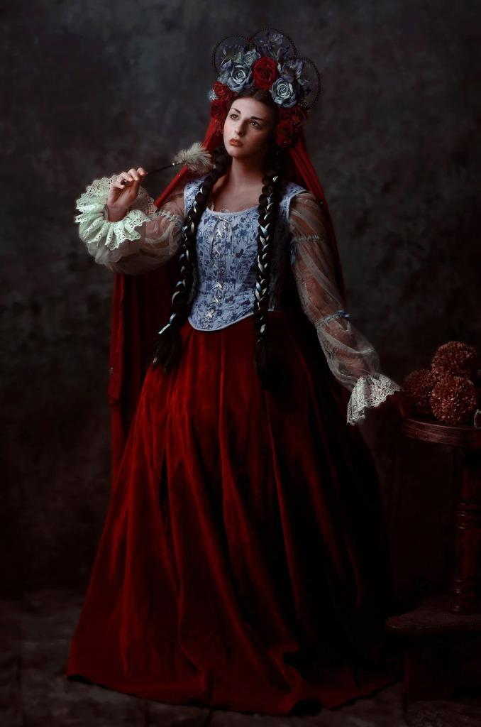 ritratto fotografico fine art rappresentante una donna in abito fantasy realizzato da Giorgia Titania con corona di fiori con in mano un pennacchio