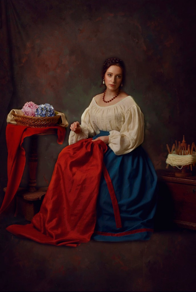 Ritratto fotografico fine art di Erica Mottin realizzato in collaborazione con la designer Elaine's Couture rappresentante una donna contadina del 1500 che cuce un mantello