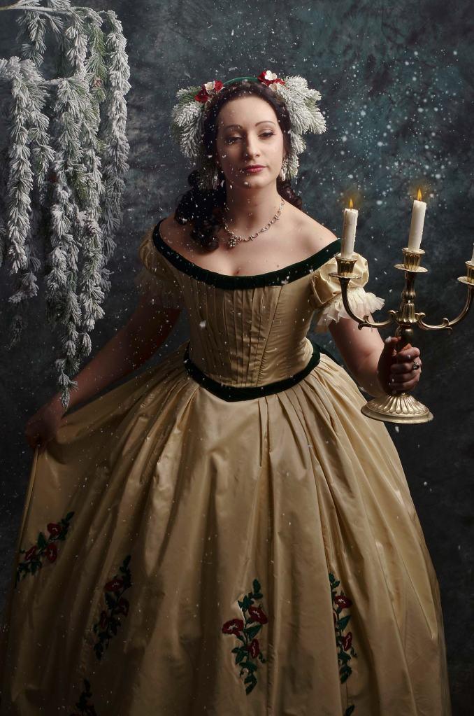 ritratto fotografico fine art rappresentante una donna in abito storico che tiene in mano un candelabro dorato mentre sta nevicando
