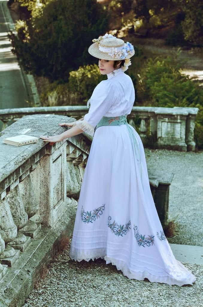 ritratto fotografico fine art di donna in abito storico edwardiano bianco con ricami verdi e cappello con fiori sulle scalinate di San Miniato a Monte a Firenze