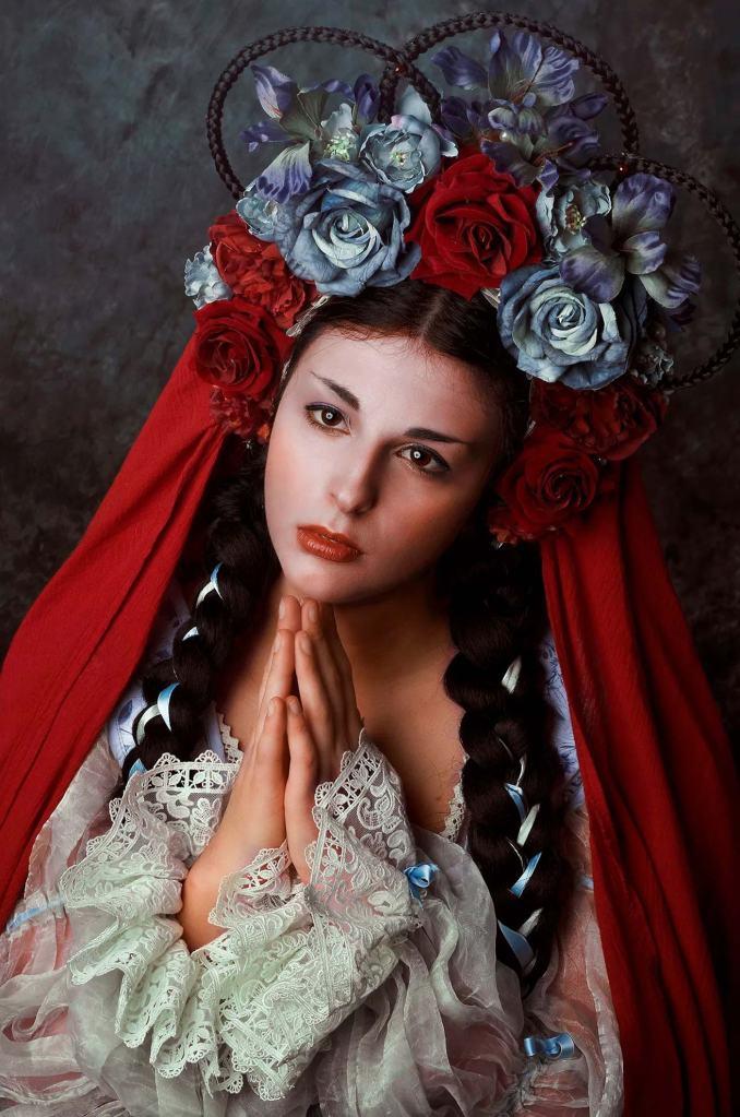ritratto fotografico fine art rappresentante una donna in abito fantasy realizzato da Giorgia Titania con corona di fiori con le mani congiunte in preghiera
